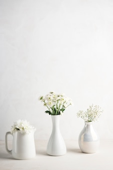 Trzy wazy z kwiatami na stole