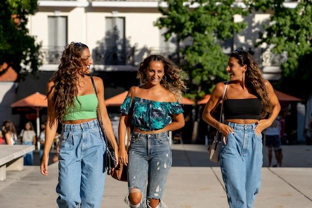 Trzy wesołe kobiety spacerujące po mieście