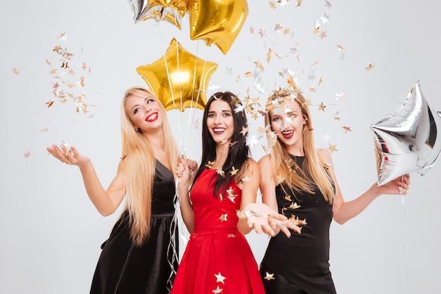 Trzy wesołe ładne młode kobiety z balonami w kształcie gwiazdy i konfetti tańczą i bawią się na białym tle