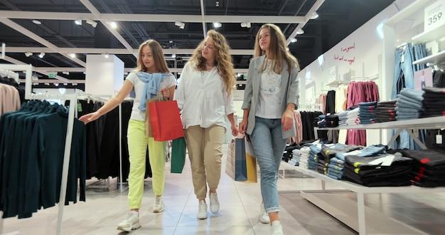 Trzy wesołe młode kobiety przechadzają się po domu towarowym w kolorowych strojach.