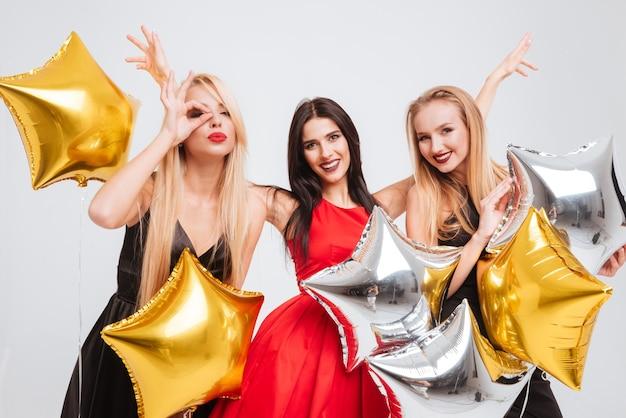 Trzy wesołe piękne młode kobiety z balonami w kształcie gwiazdy bawią się razem na białym tle