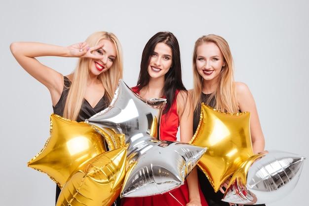 Trzy wesołe śliczne dziewczyny trzymające balony w kształcie gwiazdy na białym tle