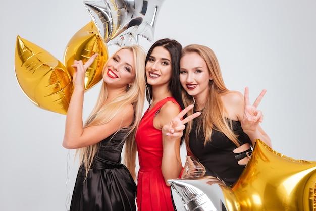 Trzy wesołe, wspaniałe młode kobiety trzymające balony w kształcie gwiazdy i pokazujące znak pokoju na białym tle