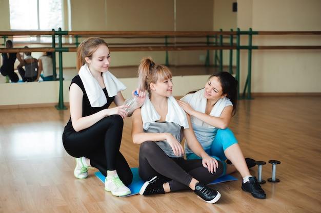 Trzy wesołej sportsmenki, śmiejąc się i bawiąc po treningu na siłowni. urocza samica odpoczywa po ciężkiej aktywności fizycznej.