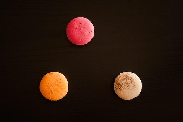 Trzy wielokolorowe macarons na czarno