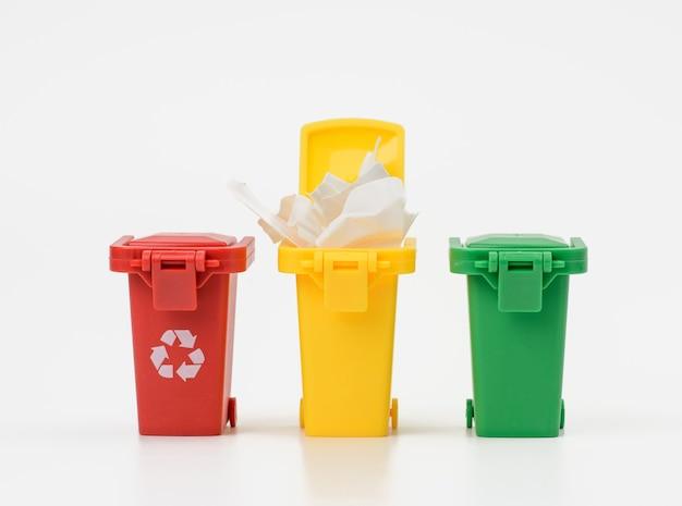 Trzy wielokolorowe plastikowe pojemniki na białym tle, koncepcja prawidłowego sortowania śmieci do dalszego recyklingu