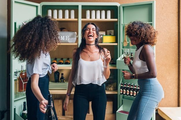 Trzy wielorasowe kobiety pijące i tańczące w nowoczesnym mieszkaniu