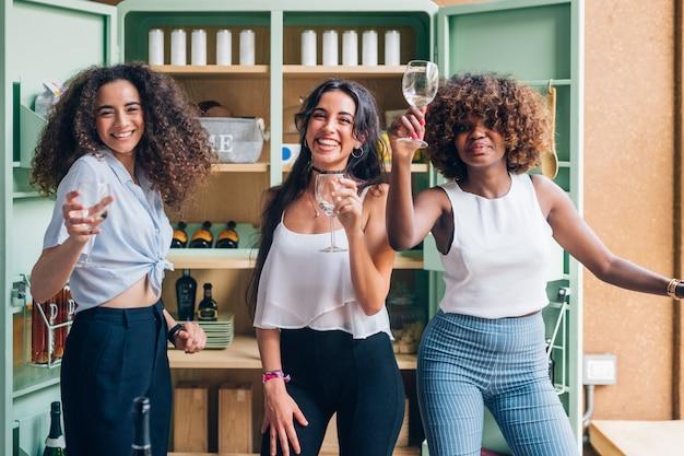 Trzy wielorasowe kobiety stojące i pijące w nowoczesnym pubie