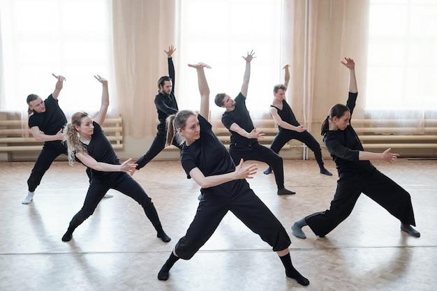Trzy wysportowane dziewczyny i czterech facetów w czarnej odzieży sportowej stojących na podłodze z wyprostowanymi nogami i ugiętymi kolanami podczas ćwiczeń w studio tańca