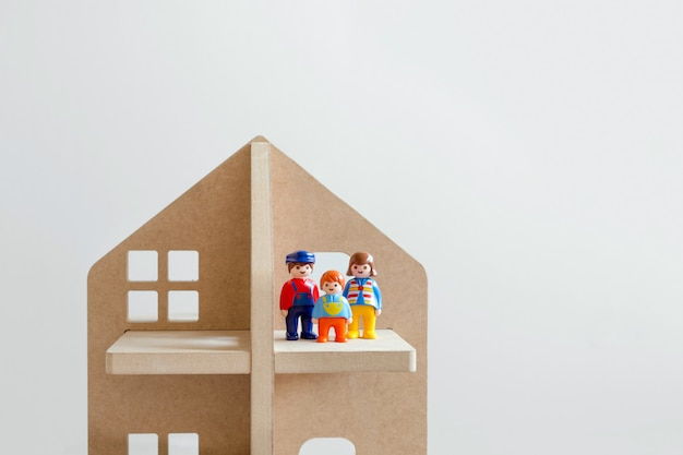 Trzy zabawkowe postacie: mężczyzna, kobieta i dziecko w drewnianym domku z zabawkami.