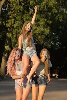 Trzy zabawne młode blondynki przyjaciółki bawią się na festiwalu holi