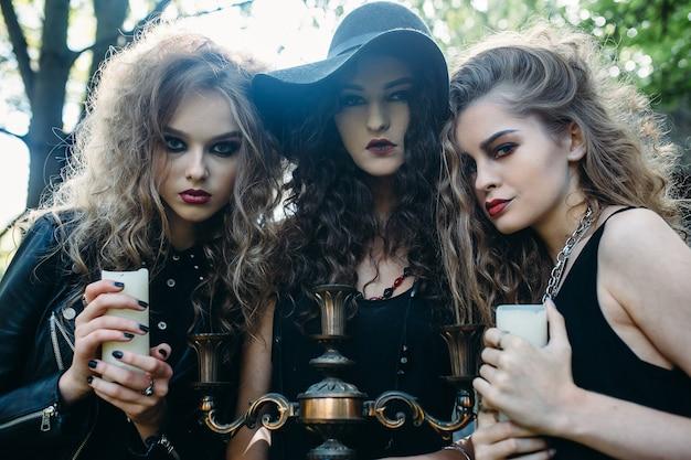 Trzy zabytkowe kobiety jako czarownice pozują przed opuszczonym budynkiem w przeddzień halloween
