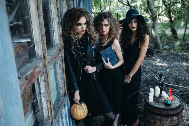 Trzy zabytkowe kobiety jako czarownice pozują w pobliżu opuszczonego budynku w przeddzień halloween