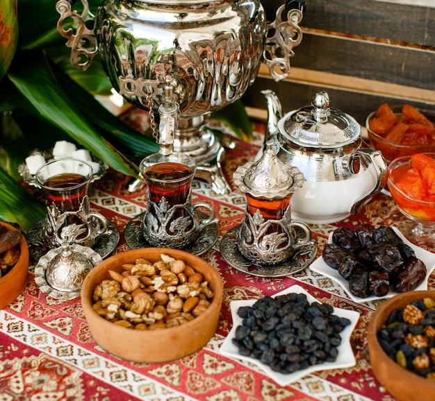 Trzy zabytkowe szklanki do herbaty, samowar, czajniczek, orzechy i suszone owoce