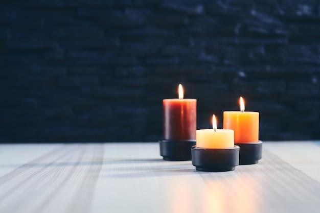Trzy zapalonej świeczki na drewnianym stole