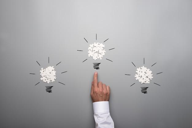 Trzy żarówki utworzone z rozrzuconych białych puzzli ręką biznesmena