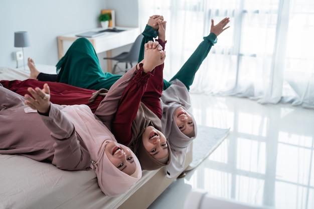 Trzy zawoalowane kobiety kładą się i podnoszą ręce na łóżku podczas wspólnej zabawy