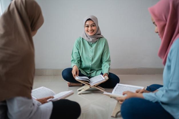 Trzy zawoalowane kobiety siedzą na podłodze i studiują koran