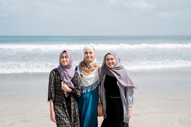 Trzy zawoalowane kobiety spędzają wakacje na plaży