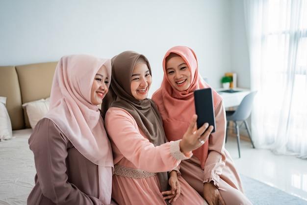 Trzy zawoalowane kobiety za pomocą smartfona