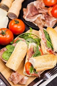 Trzy zdrowe i pyszne kanapki na drewnianej desce obok pomidorów, zieleni, szynki i sera