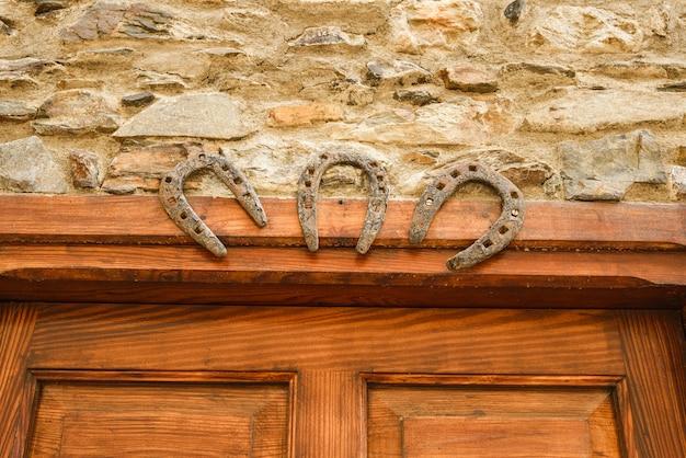 Trzy żelazne podkowy symbolizujące szczęście na drewnianych drzwiach talizman przesąd