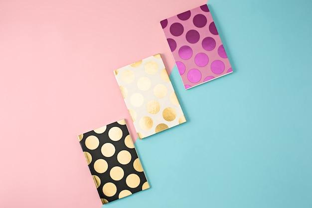 Trzy żeńskie zeszyty na kolorowym bagroundie