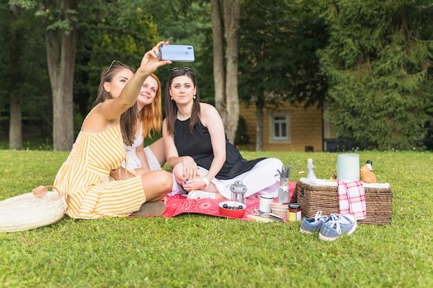 Trzy żeńskiego przyjaciela bierze selfie na pinkinie