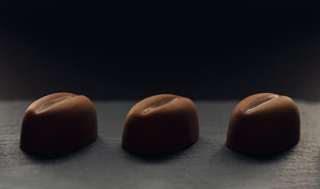 Trzy ziarna kawy kształt czekolady na ciemnym tle