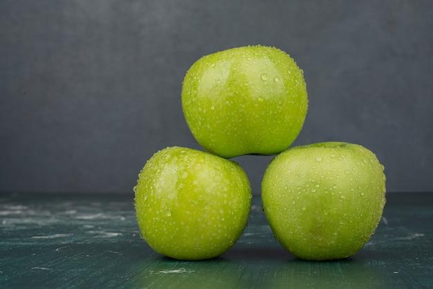 Trzy zielone jabłka na marmurowej powierzchni