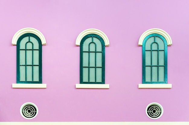Trzy zielone łukowe okna na różowej ścianie domu we włoskim stylu retro