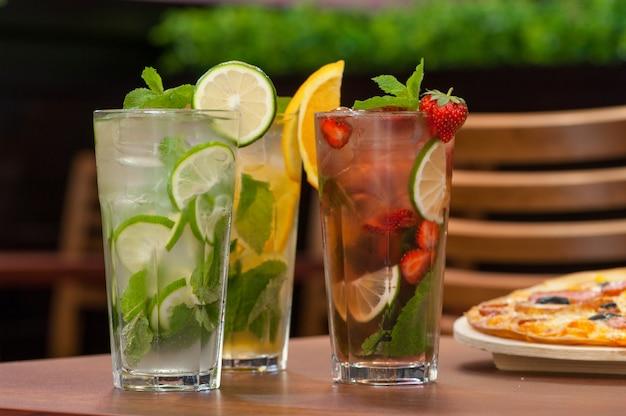 Trzy zimne napoje z cytrusami i truskawkami w szklance na stole i pizza