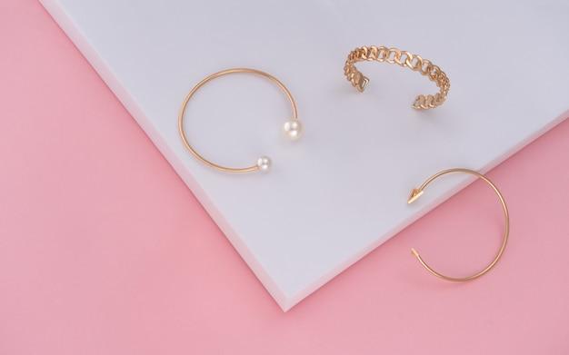 Trzy złote bransoletki na tle różowego i białego papieru z miejsca na kopię