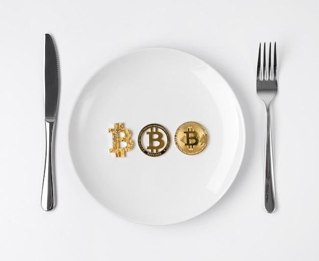 Trzy złote monety bitcoin podawane na białym pustym talerzu