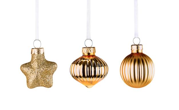 Trzy złote ozdoby świąteczne na białym tle