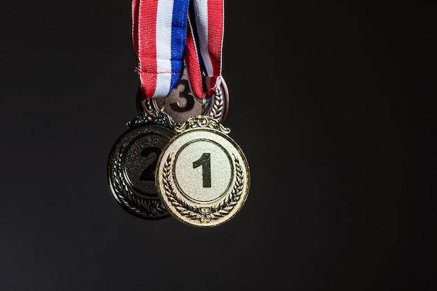 Trzy złote, srebrne i brązowe medale wiszące na ciemnym tle. koncepcja sportu i zwycięstwa.