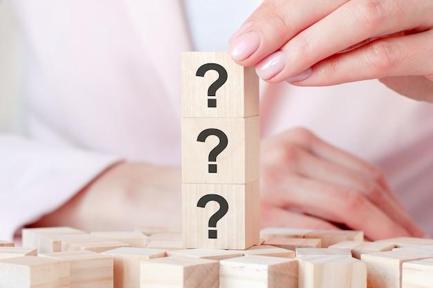 Trzy znaki zapytania napisane na drewnianych kostkach, białe tło