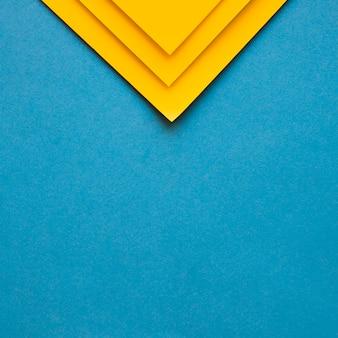 Trzy żółte kartonowe papiery na górze niebieskie tło