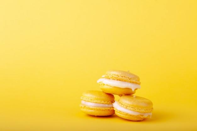 Trzy żółty cytryna makaronik w stosie na żółtym tle