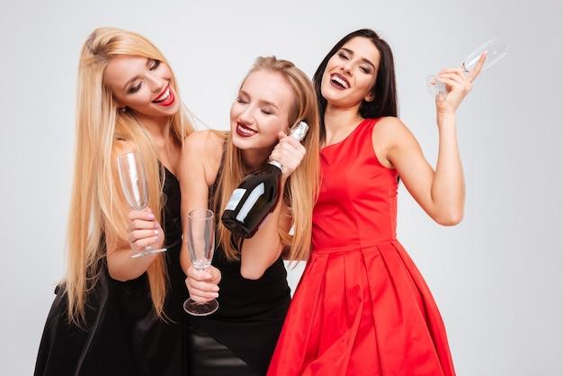 Trzy zrelaksowane atrakcyjne młode kobiety piją szampana i tańczą na białym tle