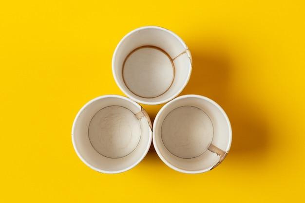 Trzy zużyte papierowe kubki ze śladami kawy