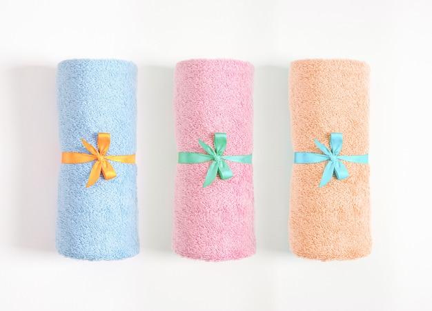 Trzy zwinięte ręczniki związane niebieską i żółtą wstążką izolowane, niebieskie, różowe i pomarańczowe ręczniki frotte na białym tle. widok z góry.