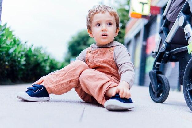 Trzyletni chłopiec ze zdziwionym gestem siedzący na ulicy w chłodny dzień