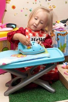 Trzyletnia dziewczynka prasuje pościel zabawkowym żelazkiem