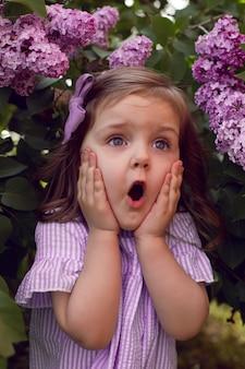 Trzyletnia dziewczynka stoi w krzakach bzu w sukience i kokardce na głowie