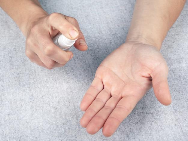 Trzyma antyseptyczny spray, dezynfekuje ręce bakterii, wirus covid-19. białe tło, widok z góry, zbliżenie. koncepcja zdrowia, higiena, spray antybakteryjny, ochrona