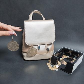 Trzyma biżuterię kolczyki z torebką kobiety na białym tle