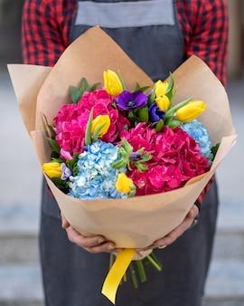 Trzyma bukiet kwiatów z rozmycie tła