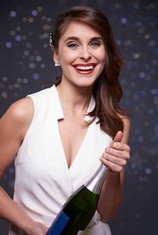 Trzyma butelkę dobrego szampana