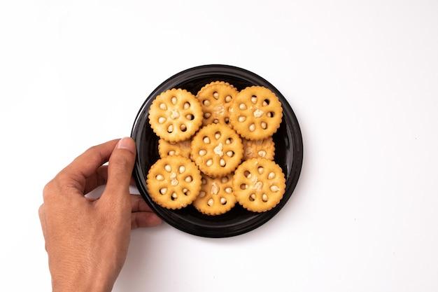 Trzyma chleb na czarnym talerzu na białym tle